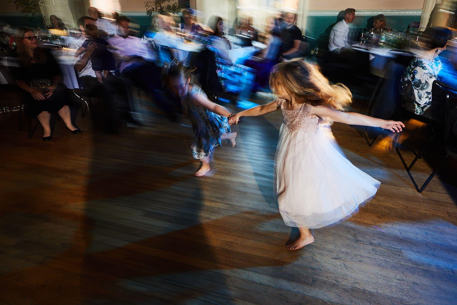 Children run across a dance floor at the marriage of her parents