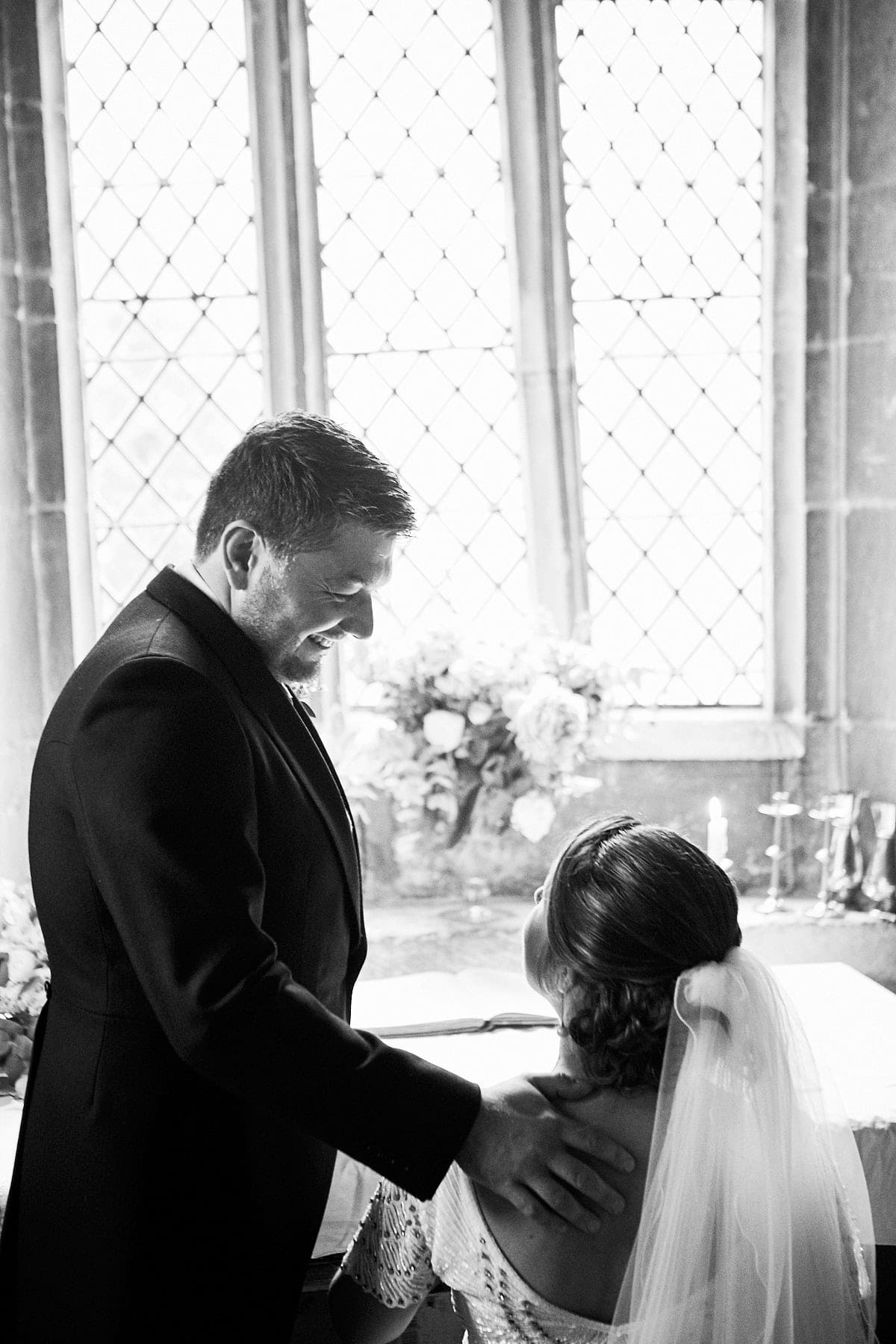 A couple look lovingly as they sign the register at Howell Manor Church