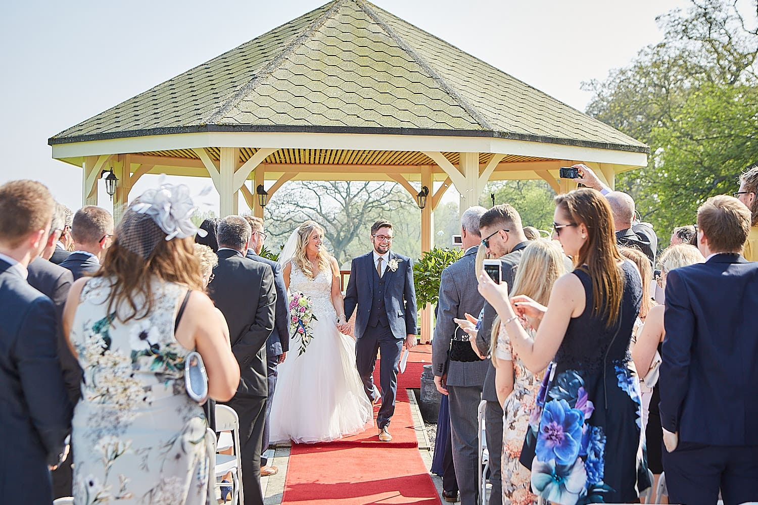 A couple walk down the aisle outdoors after being married in Louth