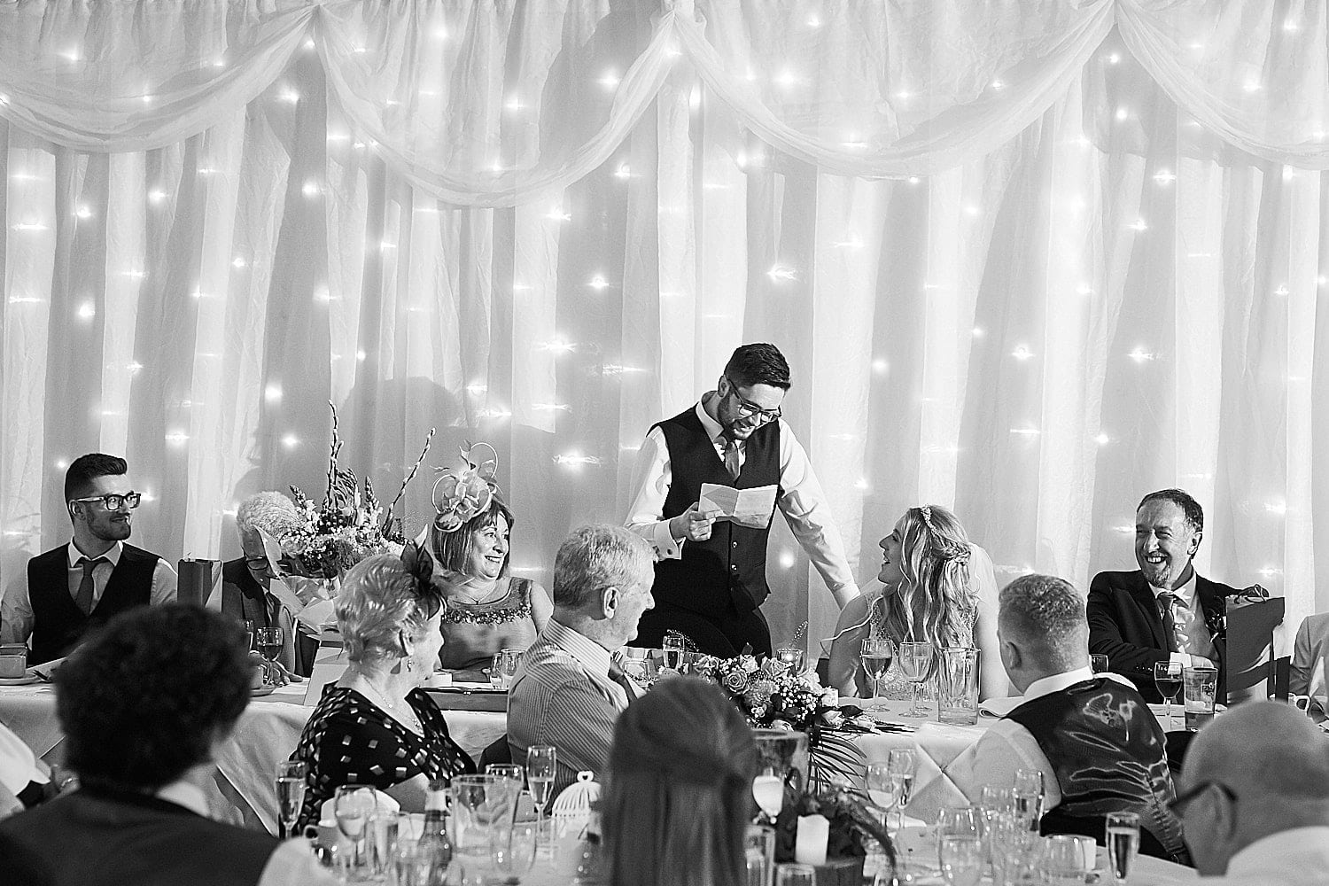 A groom reads his speech whilst looking lovingly at his new wife.