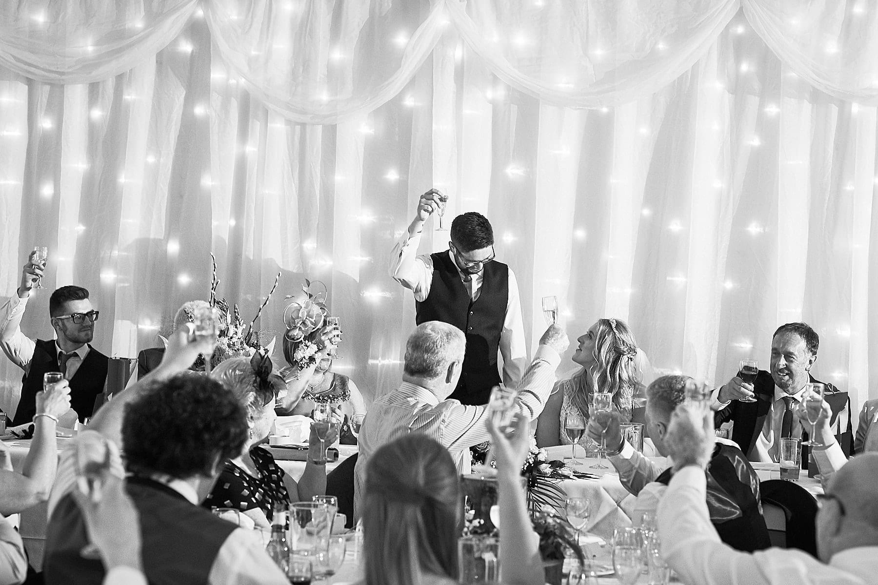 A groom raises a toast on his wedding day