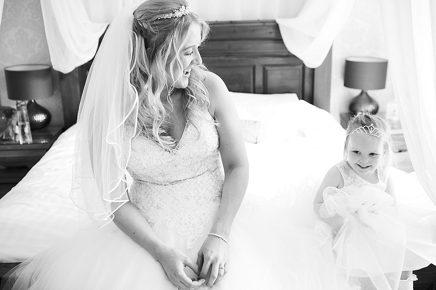 A bride sits on the bed of the bridal suite and laughs with her flower girl on her wedding day