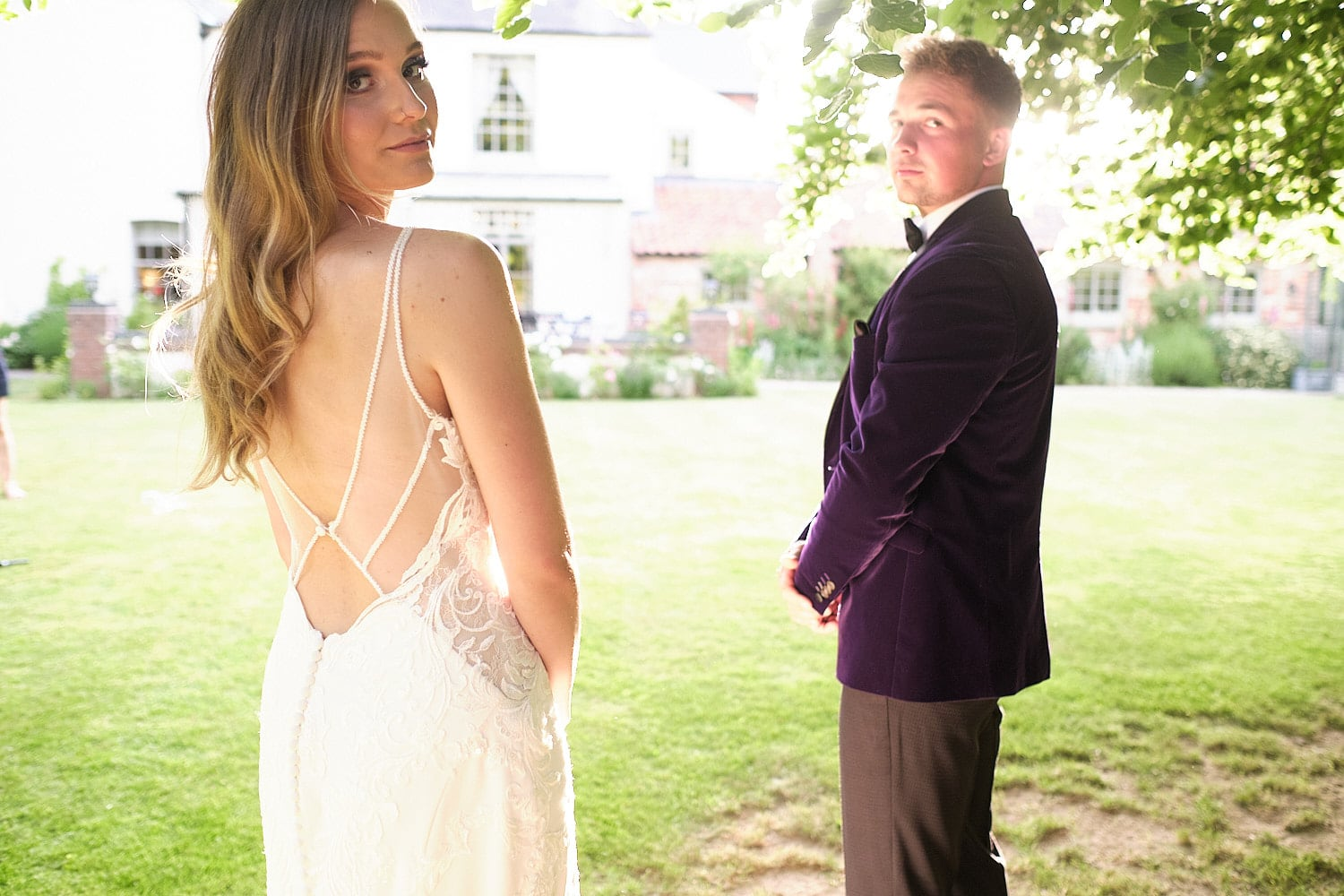 A bride and groom look over their shoulder towards the camera at a Lincolnshire wedding