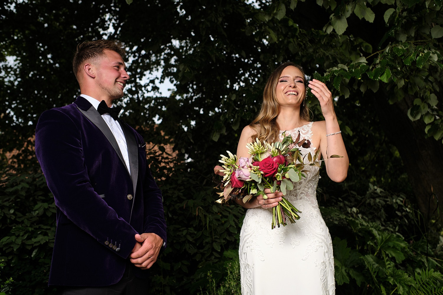 A bride & Groom laugh out loud at a we3dding at the elm tree Hundelby